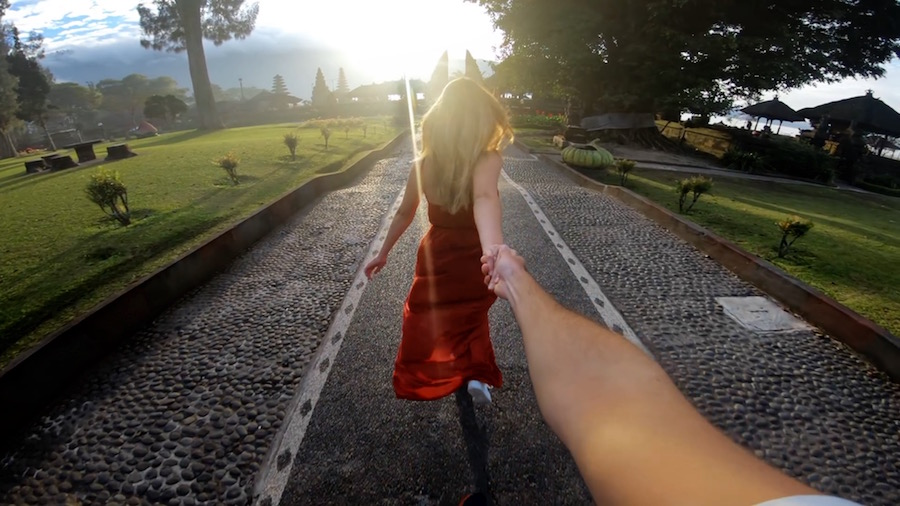 girl with arm outstretched leading the photographer